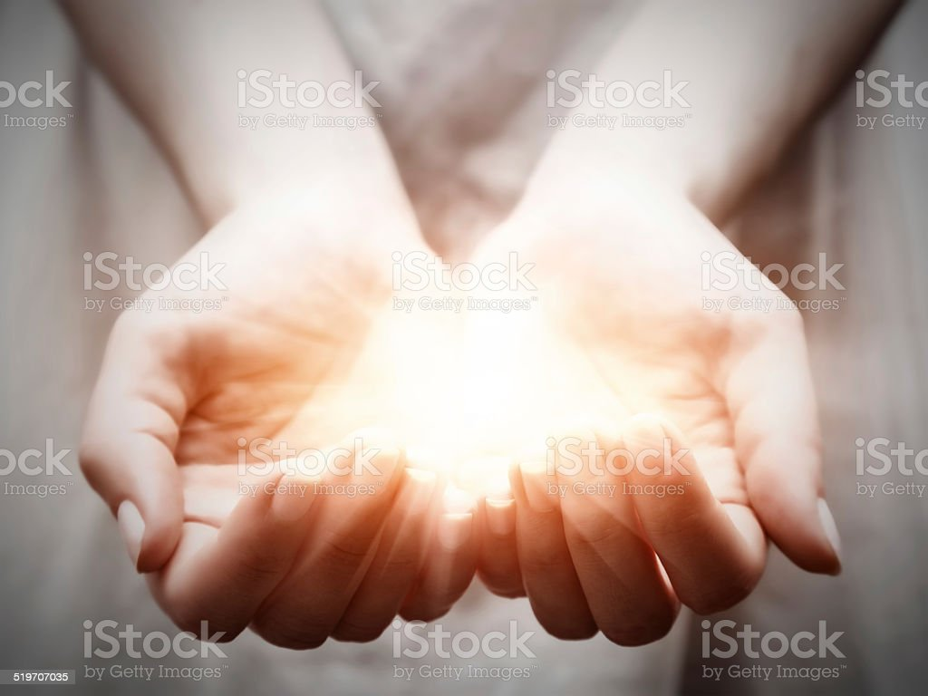 The light in young woman hands. Sharing, giving, offering, protection stock photo