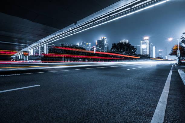 de ljusa spåren på den moderna byggnadens bakgrund - road bildbanksfoton och bilder