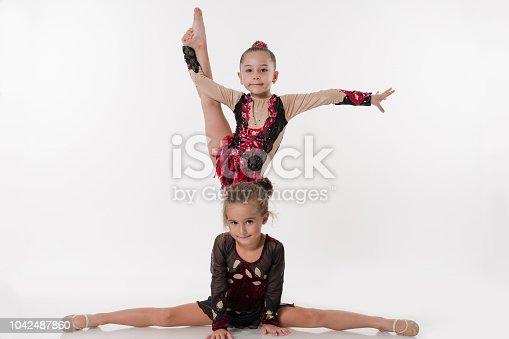 1160198096 istock photo The little acrobatic ballerina dancer's doing the splits 1042487860