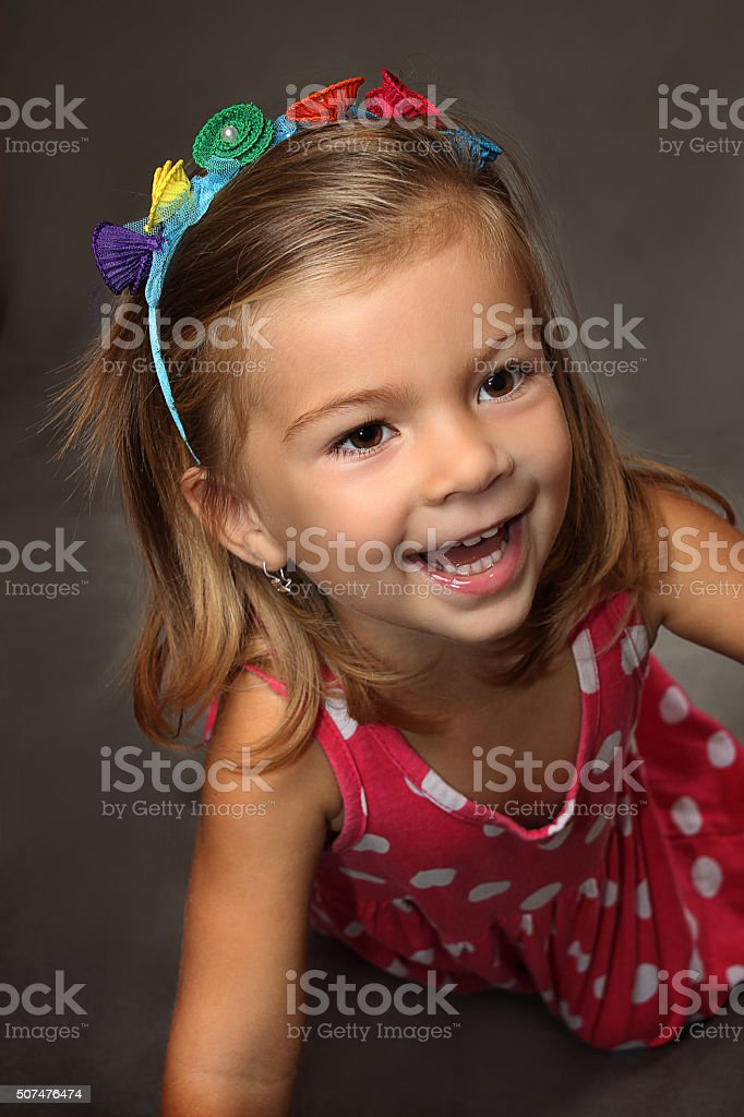 the little amusing girl in a red dress stock photo
