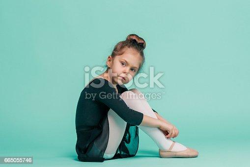 819677734 istock photo The little balerina dancer on blue background 665055746