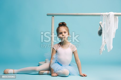 819677734 istock photo The little balerina dancer on blue background 665058960