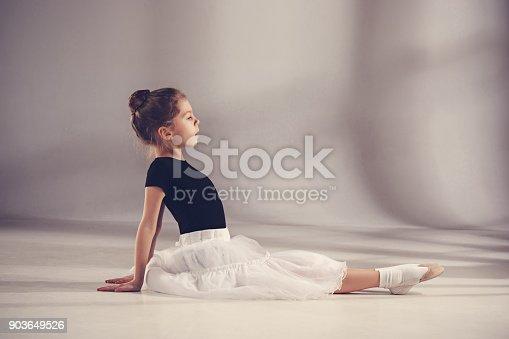 819677734 istock photo The little balerina dancer on gray background 903649526