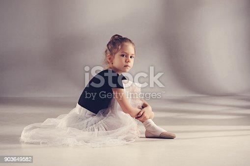 819677734 istock photo The little balerina dancer on gray background 903649582