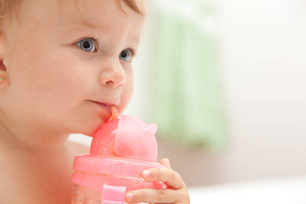 The little blue-eyed baby girl drinks juice from a bottle stock photo