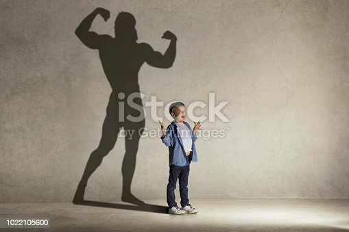 istock The little boy dreaming about athletic bodybuilder figure with muscles 1022105600