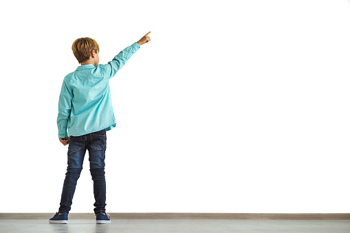 The little boy gesturing on the white wall background