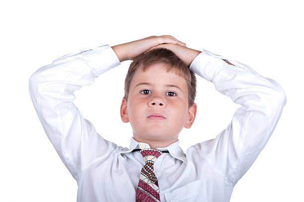 O menino coloca as mãos na cabeça - foto de acervo