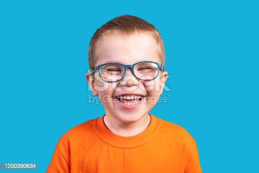 The little boy in glasses laughs. Isolated on a blue background.For any purpose.