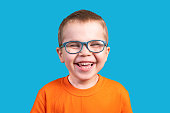 istock The little boy in glasses laughs. Isolated on a blue background. 1200390634