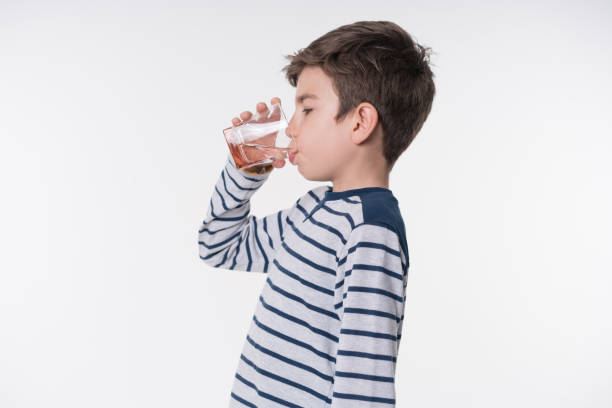 der kleine junge ist trinkwasser mit pille - innocent saft stock-fotos und bilder