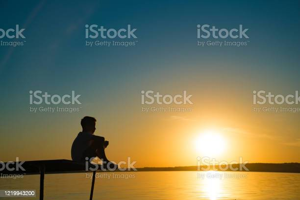 Photo of the little boy sits on a bridge and looks at sunset by the river.