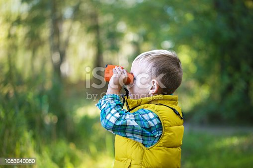 The little boy young researcher looks up and exploring with binoculars environment in the green forest on a sunny day