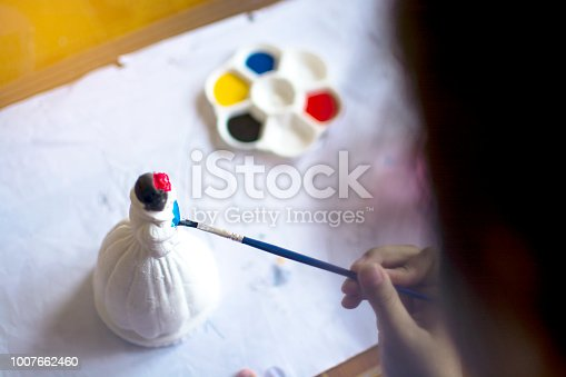 istock The little child painting plaster doll with blue water colour, practice art concept, selective focus on painting brush 1007662460