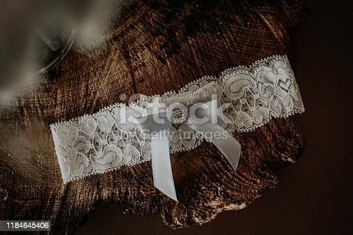 A bride's lace garter belt on top of a piece of wood