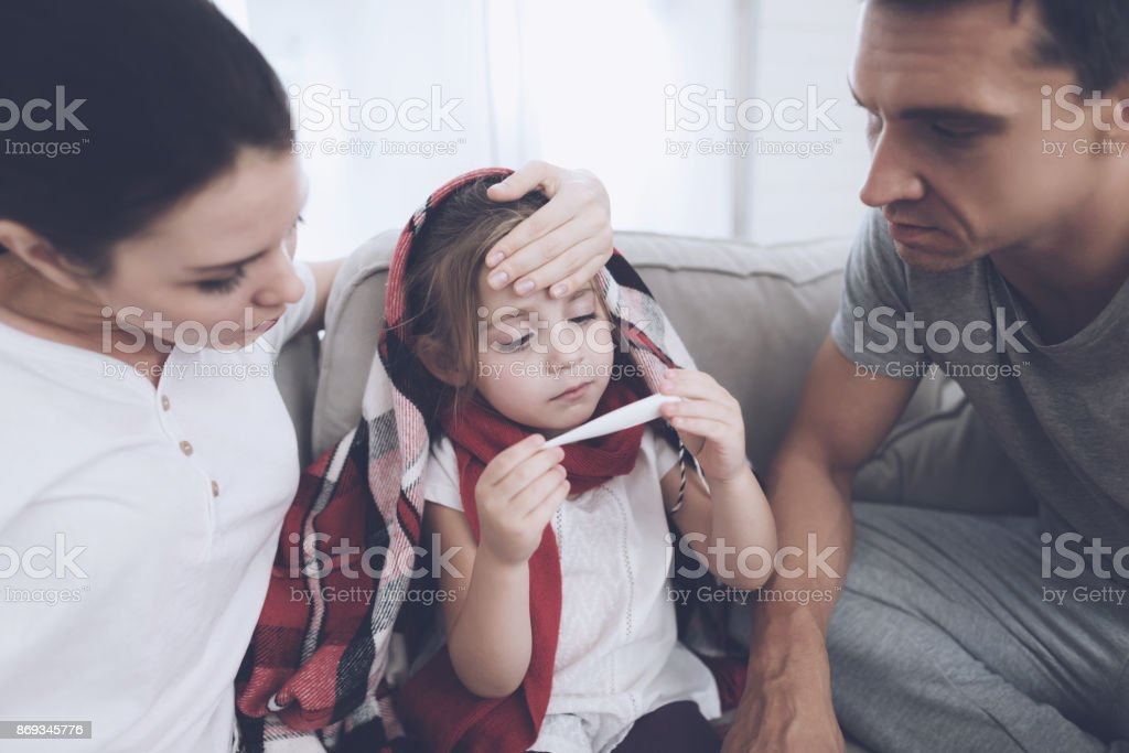 The little girl caught a cold. Her mother and father are treating her. The girl is looking at the thermometer. stock photo