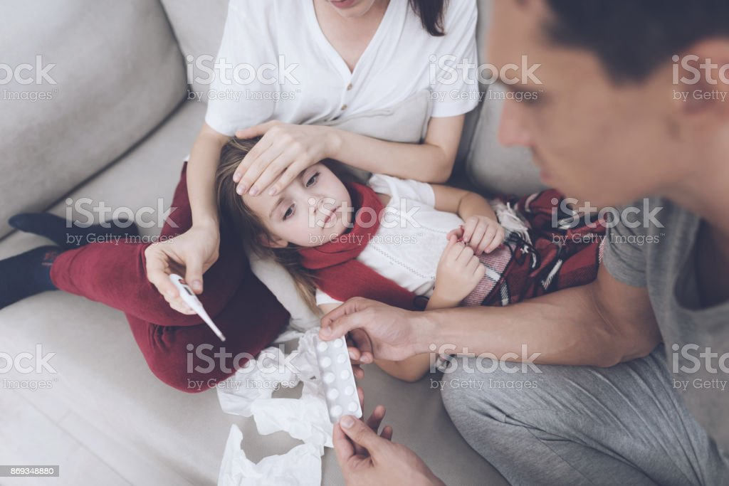 The little girl caught a cold. Her mother and father are treating her. The girl lies on her mother's lap stock photo