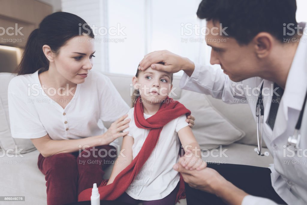 The little girl caught a cold. Her mother called the doctor at home. The doctor examines the girl stock photo