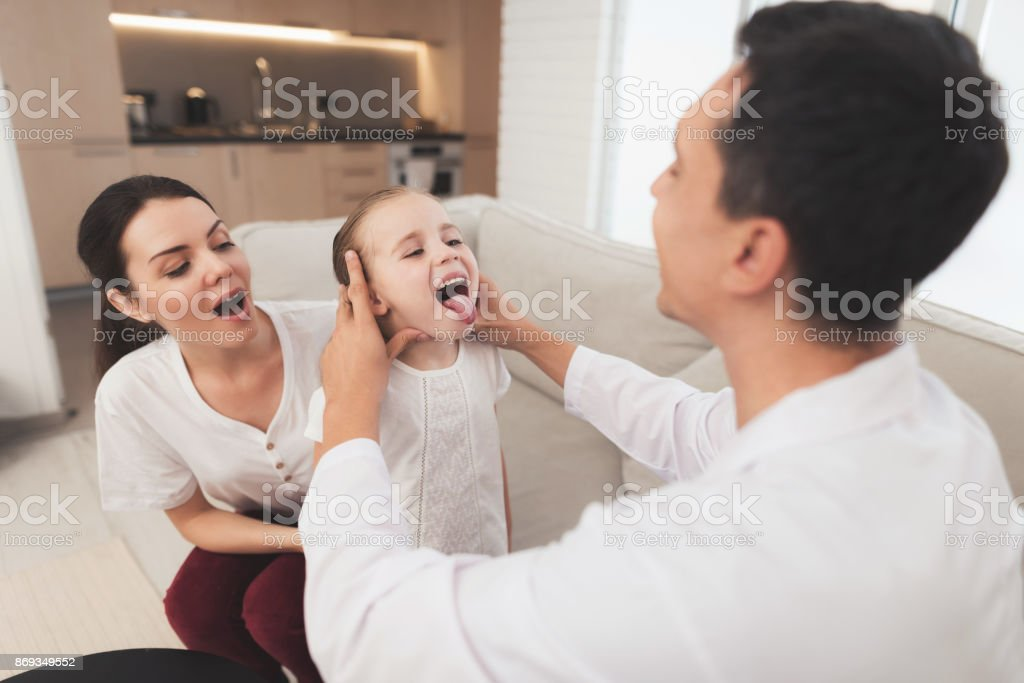 The little girl caught a cold. Her mother called the doctor at home. Doctor looks at the girl's throat stock photo