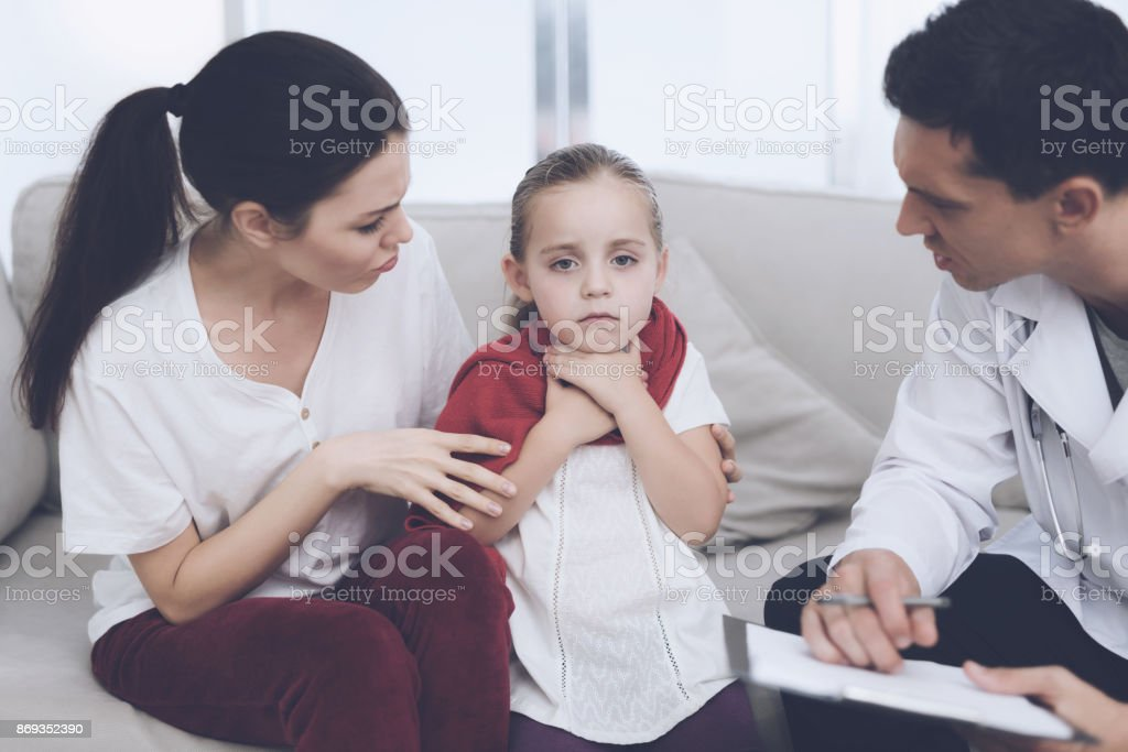 The little girl caught a cold. Her mother called the doctor at home. Doctor interrogates the girl stock photo