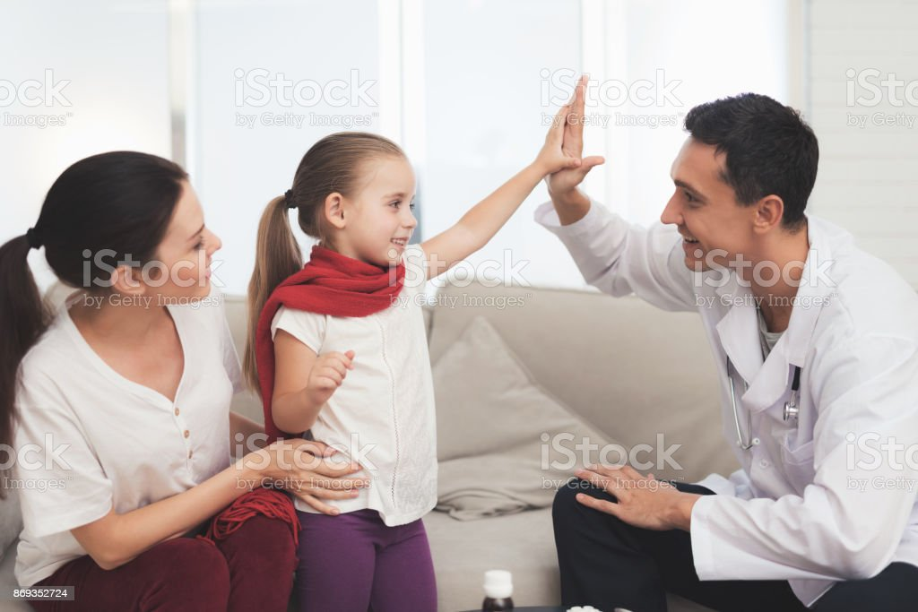 The little girl caught a cold. Her mother called the doctor at home. The girl gives the doctor high five stock photo