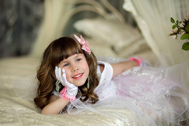 die kleines mädchen in einem abendkleid auf einem bett - schmuck engel stock-fotos und bilder
