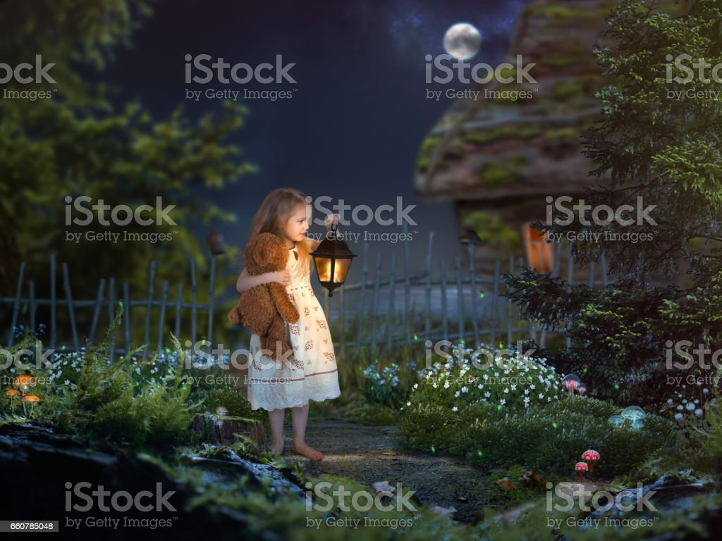 The little girl in the night in a beautiful magical forest. Girl holding an antique lantern and a toy bear. Children's fairy tale stock photo