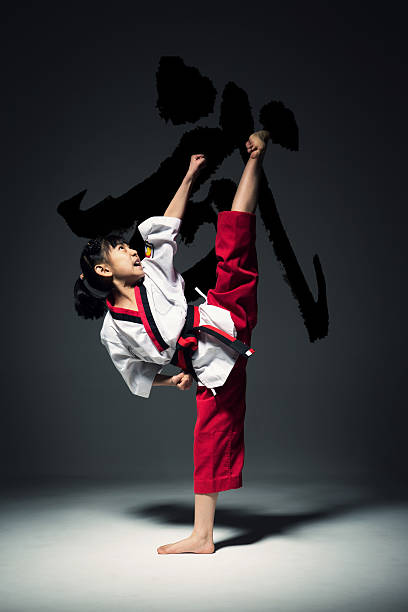 The little girl is practising Taekwondo. stock photo