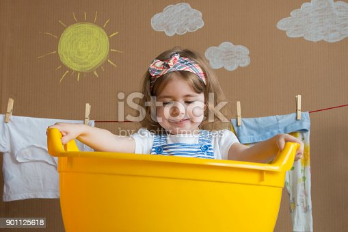 istock The little girl is washing clothes and hanging on a rope is drying. Conceptual housework. baby helps mom 901125618