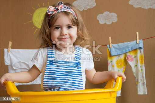 istock The little girl is washing clothes and hanging on a rope is drying. Conceptual housework. baby helps mom 901125724