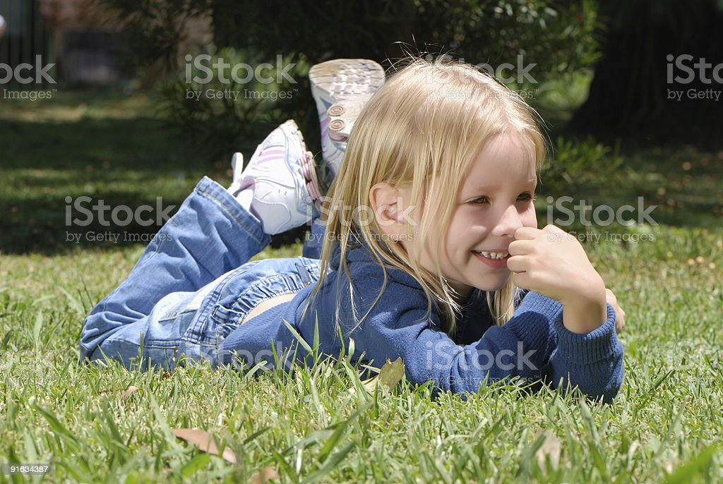 The little girl laying on a grass in park royalty-free stock photo