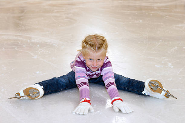 The little girl sitting on ice in ice skating. stock photo