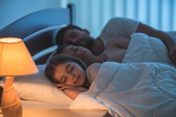 das kleine mädchen in der nähe von den eltern im bett schlafen. nachtzeit - nachttischleuchte touch stock-fotos und bilder