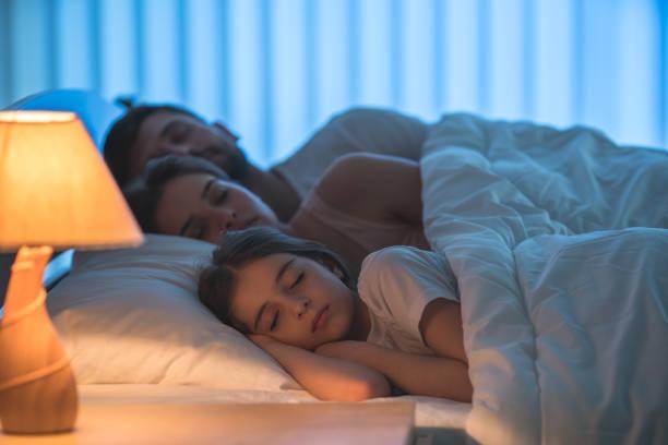 das kleine mädchen schlief in der nähe der eltern im bett. nacht - nachttischleuchte touch stock-fotos und bilder