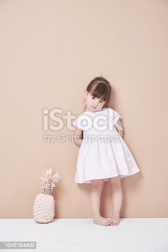 istock The little girl stood in front of the wall in a white dress, lively and lovely. 1045164400