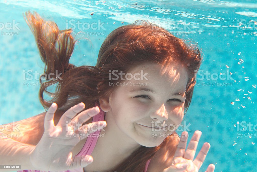 The little girl swimming underwater and smiling stock photo