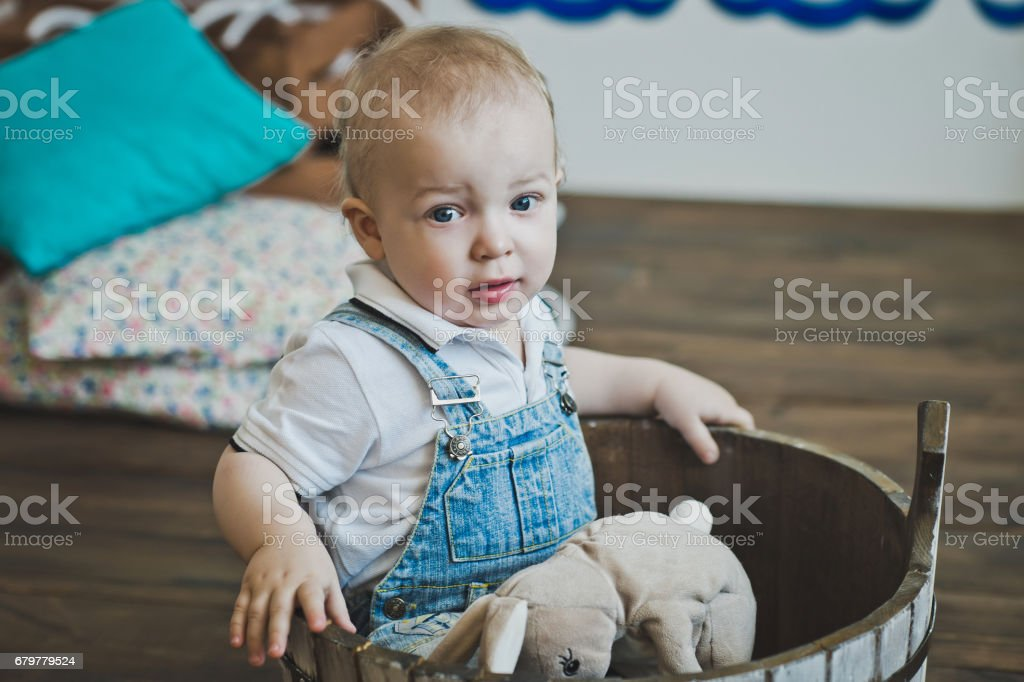 The little one-year-old child is seated in a wooden basin 5520. stock photo
