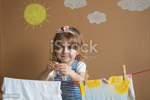 istock The little pretty girl Hand Putting Clothespin and hangs out to dry a clothes. Conceptual housework. baby helps mom 901125354