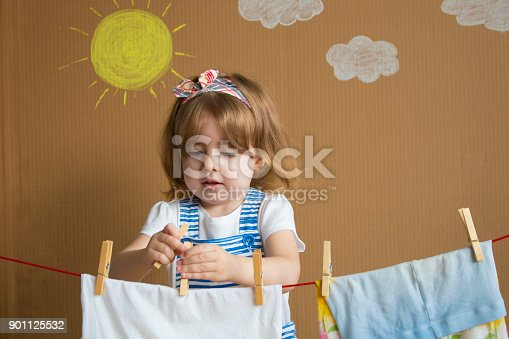 istock The little pretty girl Hand Putting Clothespin and hangs out to dry a clothes. Conceptual housework. baby helps mom 901125532