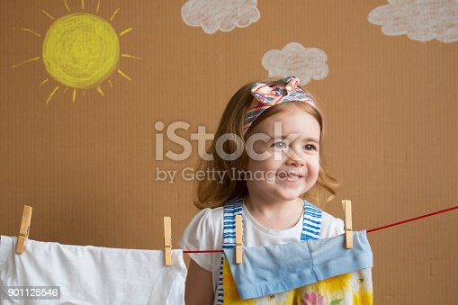 istock The little pretty girl Hand Putting Clothespin and hangs out to dry a clothes. Conceptual housework. baby helps mom 901125546