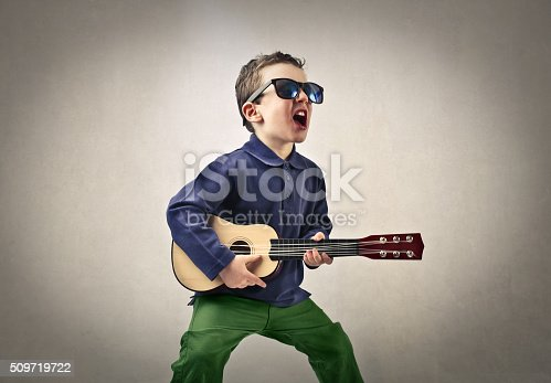 A kid singing enthusiastically with his little guitar