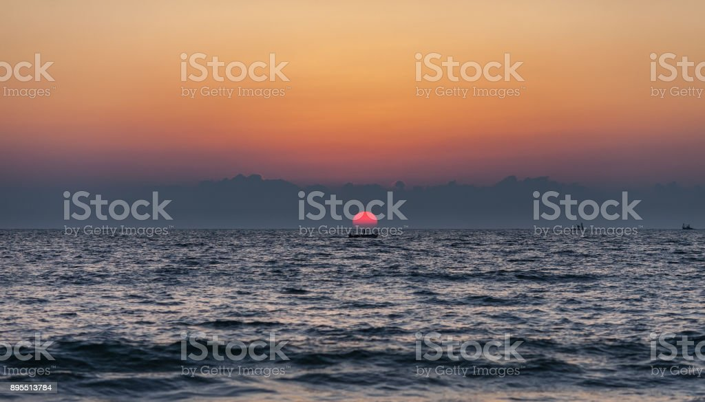 The lonely fisherman stands in the boat stock photo