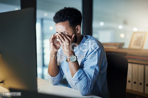 Shot of a young businessman rubbing his eyes while working on a computer in an office at night