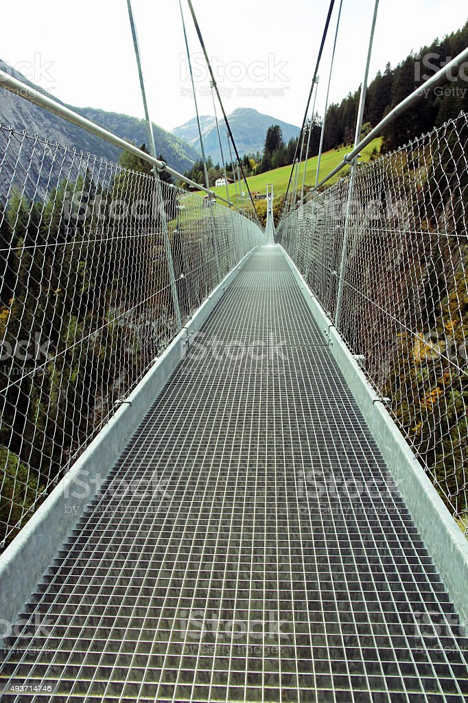 The long suspension bridge in the mountains stock photo
