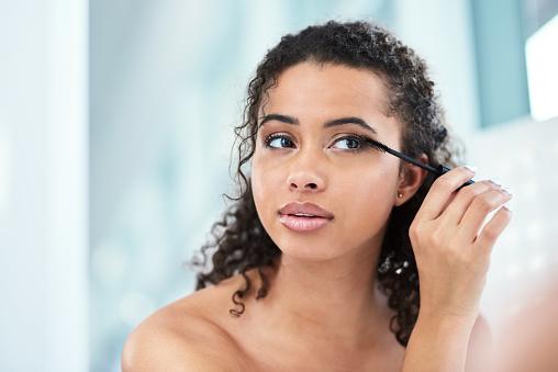 Shot of a beautiful young woman applying mascara in her bathroom mirror