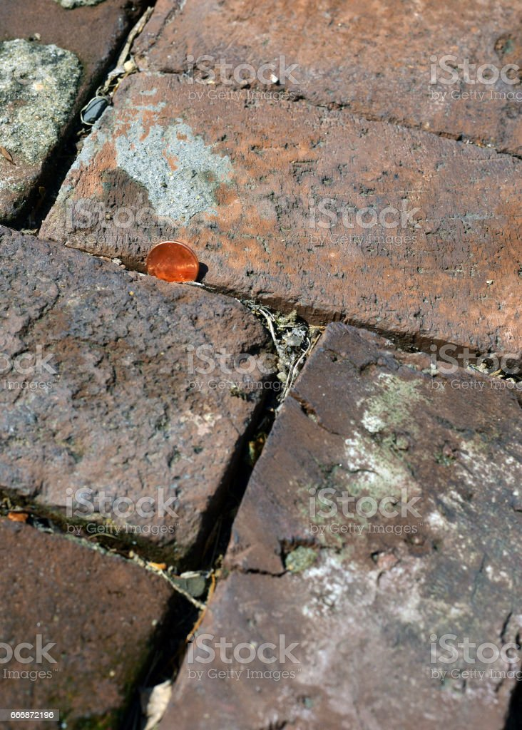 a lost penny is lying in the brick gap.
