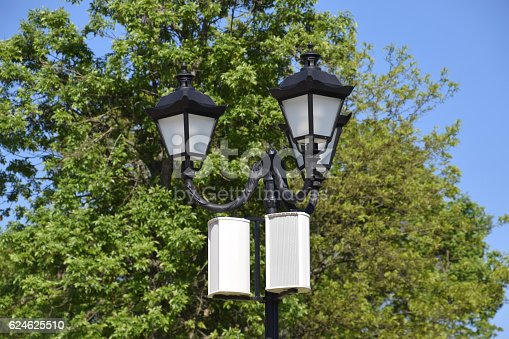 The loudspeaker on the pole. Outdoor speakers for fun walking in the park. A pillar with lights and speakers