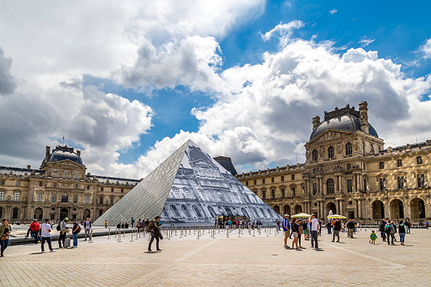 The Lourve Paris, France - June 17, 2016: A daytime HDR shot of the Lourve in Paris.  The Lourve is visited by thousands of tourists every year and you can see some of them roaming the grounds in this photo. musee du louvre stock pictures, royalty-free photos & images