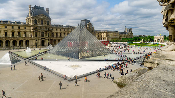 The Louvre, Paris Paris, France May 28 2015: The Louvre Pyramid and buildings with many tourists and visitors walking around. musee du louvre stock pictures, royalty-free photos & images