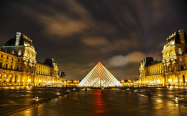 The Louvre Pyramid in Paris at night Paris, France - October 12, 2014: The Louvre Pyramid in Paris, France. It serves as the main entrance to the Louvre Museum. Completed in 1989 it has become a landmark of Paris. musee du louvre stock pictures, royalty-free photos & images